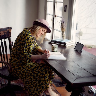 Young woman writes at rustic desk